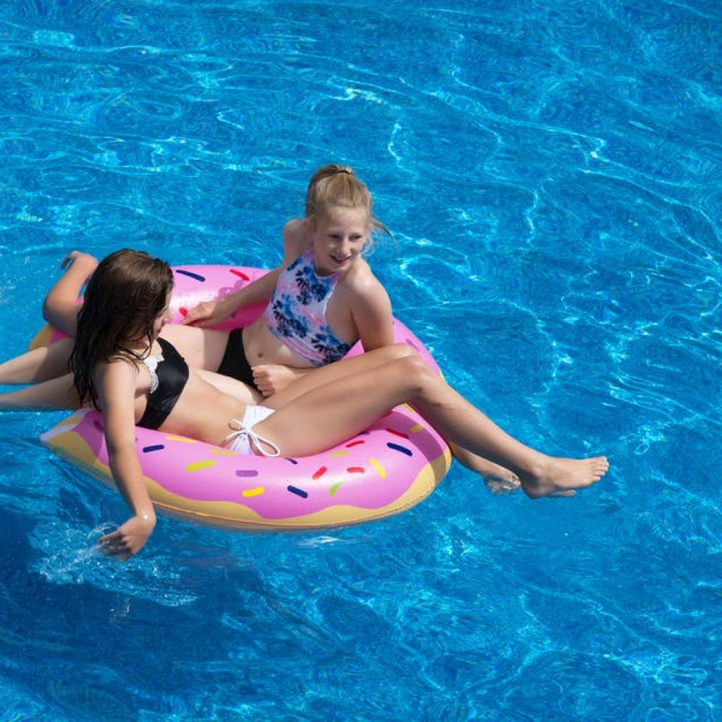 mom and daughter swimming in an above ground pool in a pink frosted donut pool float