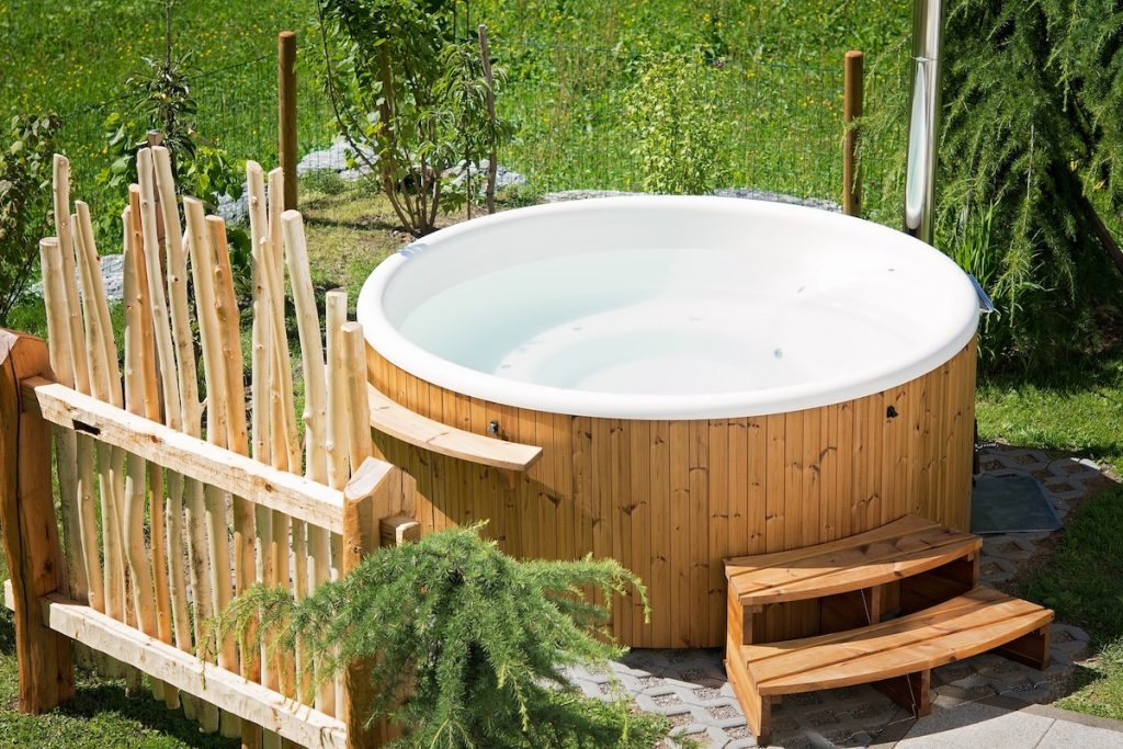 Wooden hot tub in backyard with wooden steps and wooden fence